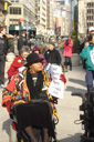photo of demonstrators, most of whom in wheelchairs, heading to Taxi of Tomorrow site