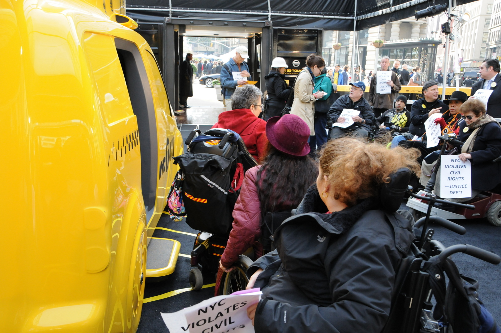 photo of demonstrators in wheelchairs unable to get into the inaccessible Taxi of Tomorrow