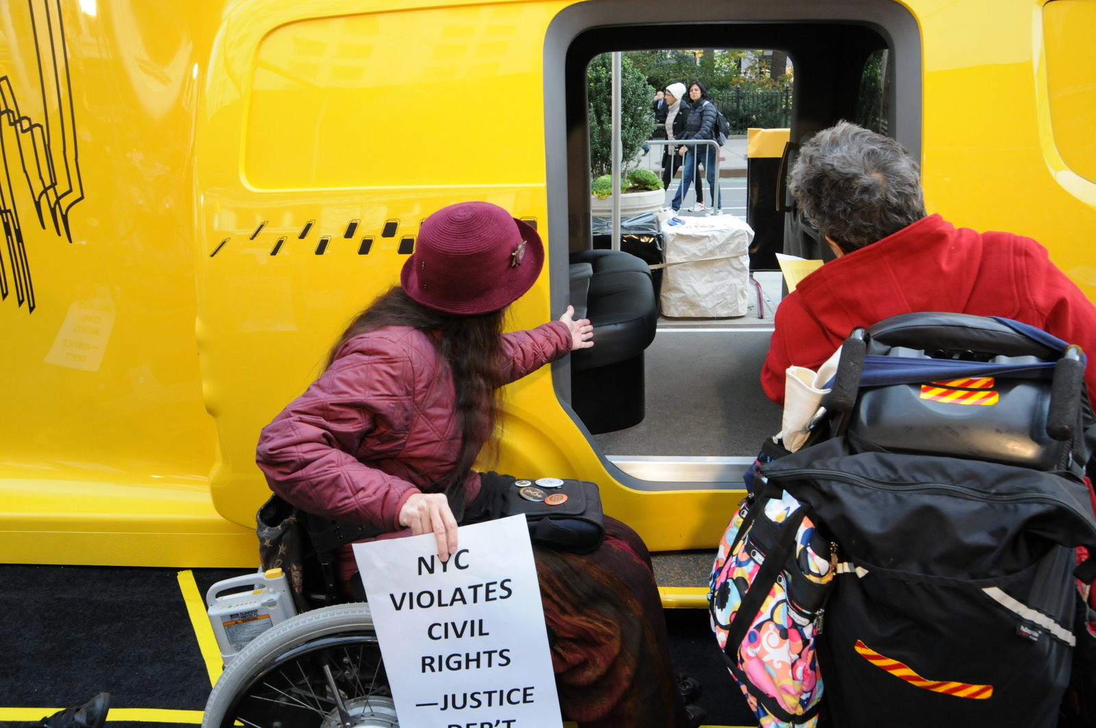 photo of two demonstrators in wheelchairs looking at Taxi's inaccessible entrance