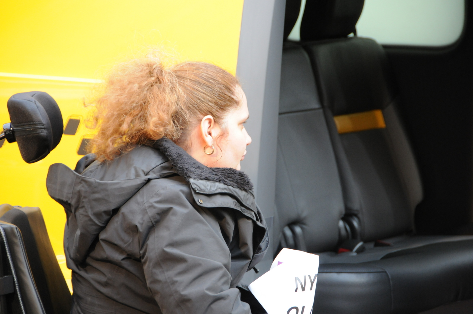 photo of female demonstrator in wheelchair looking at Taxi's inaccessible entrance